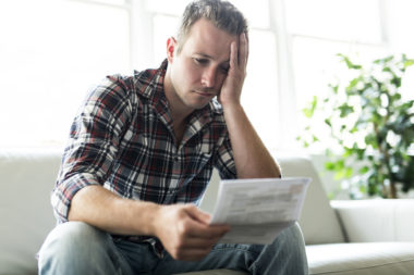 A frustrated person reading over financial documents on their couch.