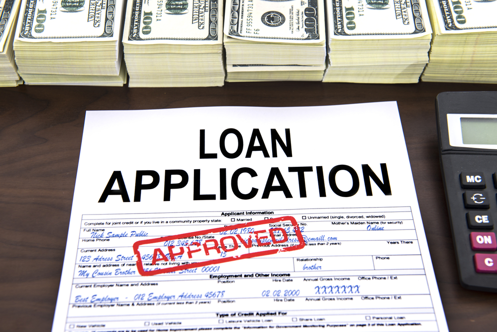 """A loan application is rubberstamped """"approved"""" next to stacks of cash."""