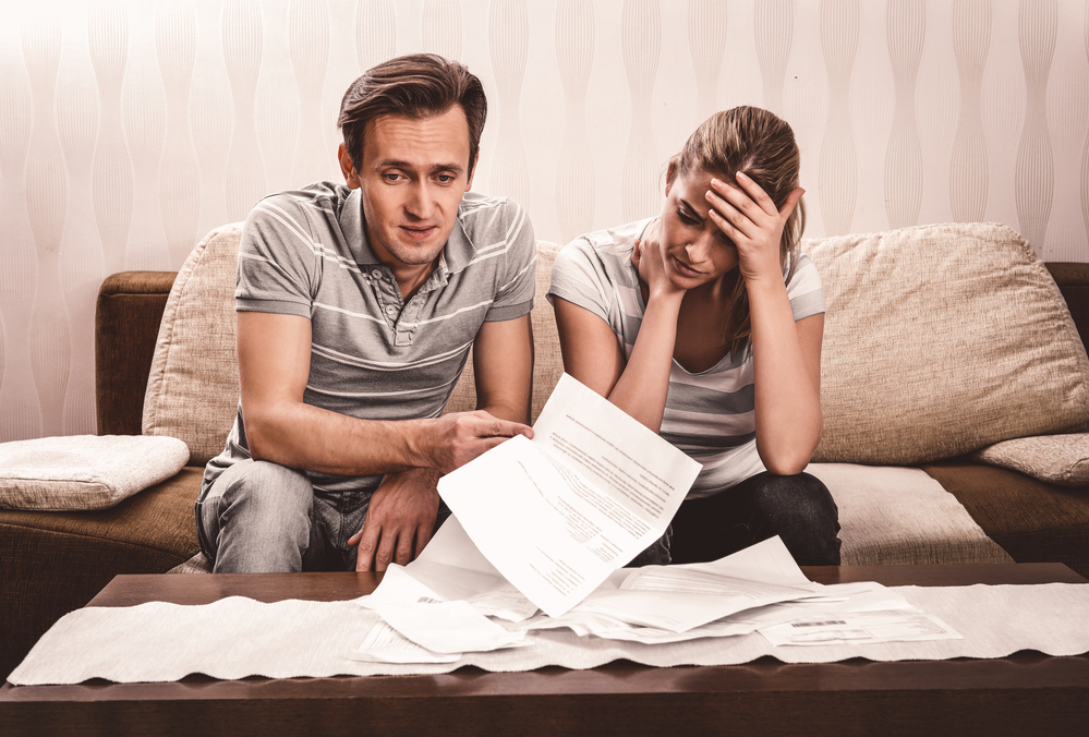 A worried couple on the couch going through financial documents.