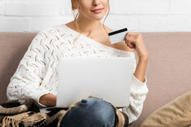 A person holds their credit card while using their laptop to shop online.