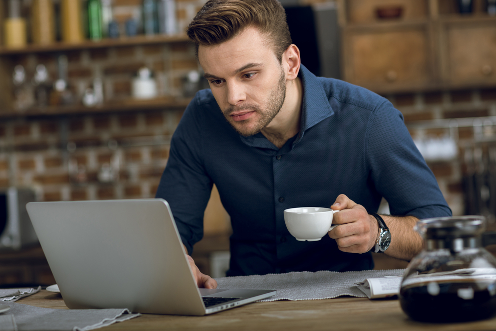 A person holding a coffee cup while working on their laptop.