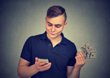 A person holds their phone on one hand while holding a fan of $100 bills in the other.