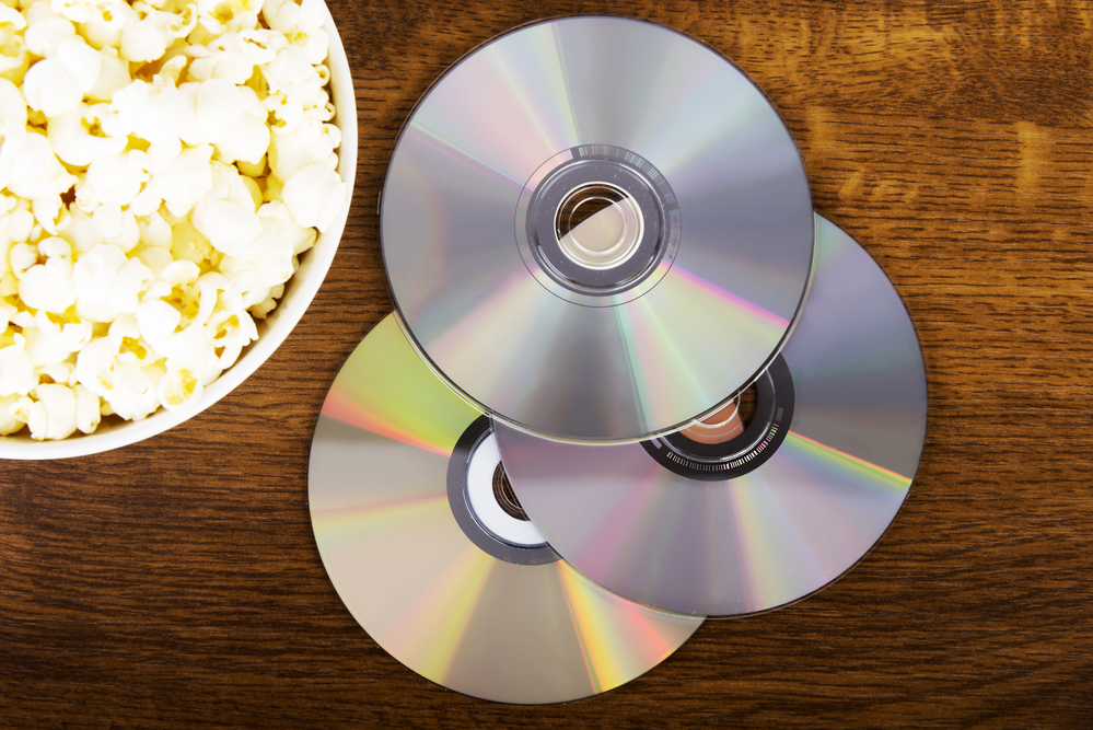 A bowl of popcorn sits next to a stack on DVDs.