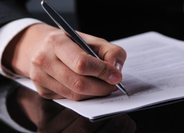 A person signing a loan contract.
