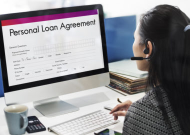 """A loan representative using a computer, which displays a screen that reads """"personal loan agreement."""""""