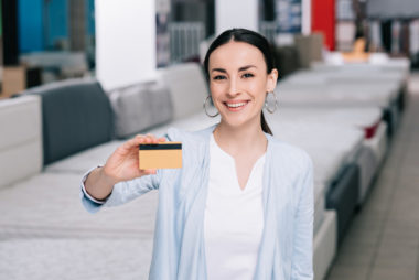 A person standing in a store, holding a credit card for the camera.