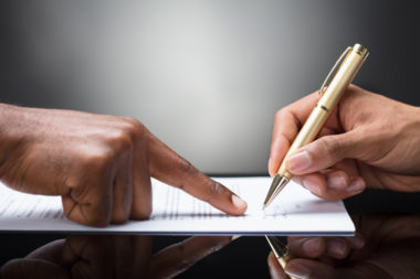 A mortgage lender points to a contract as a person signs it.