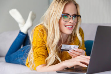 A person wearing a yellow shirt lies on their stomach while holding a credit card and shopping on their laptop.