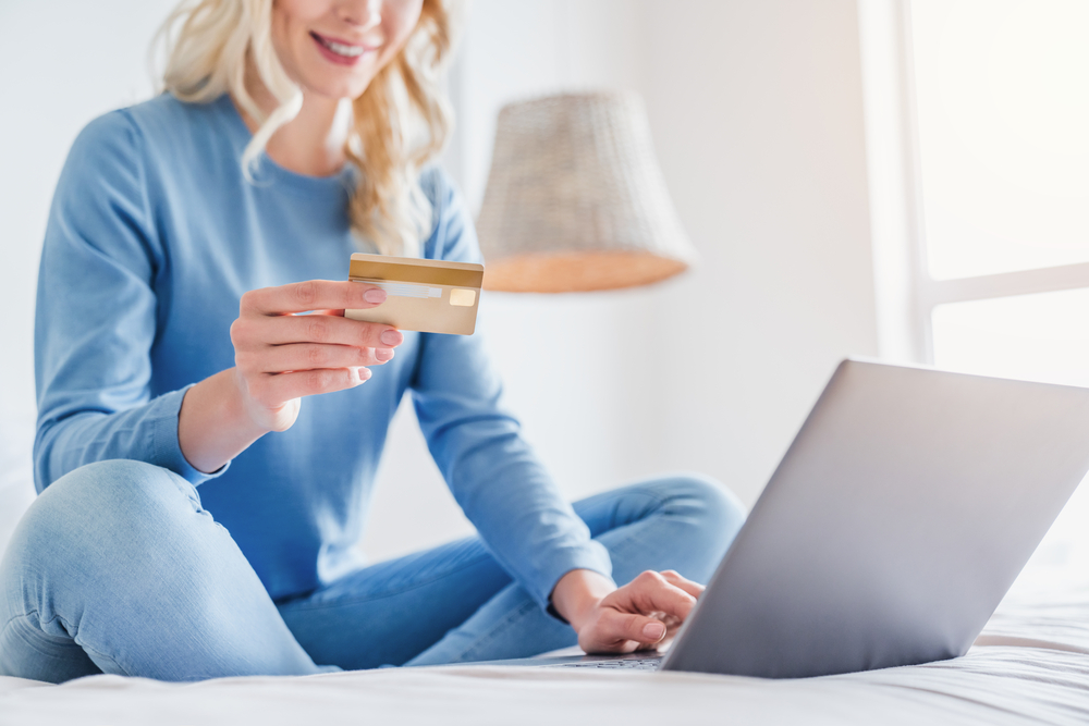 A person sitting on their bed, holding a credit card as they shop on their laptop.