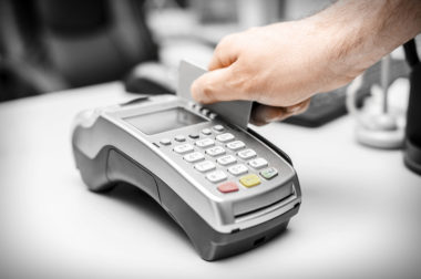 A credit card being swiped through a retail pay terminal.